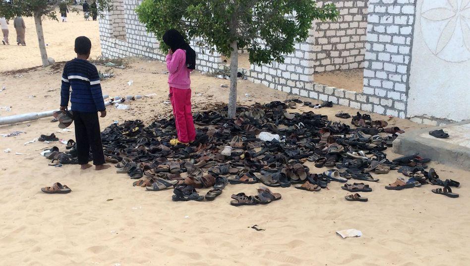 Kinder stehen rund um einen Haufen Schuhe der Opfern des Attentats