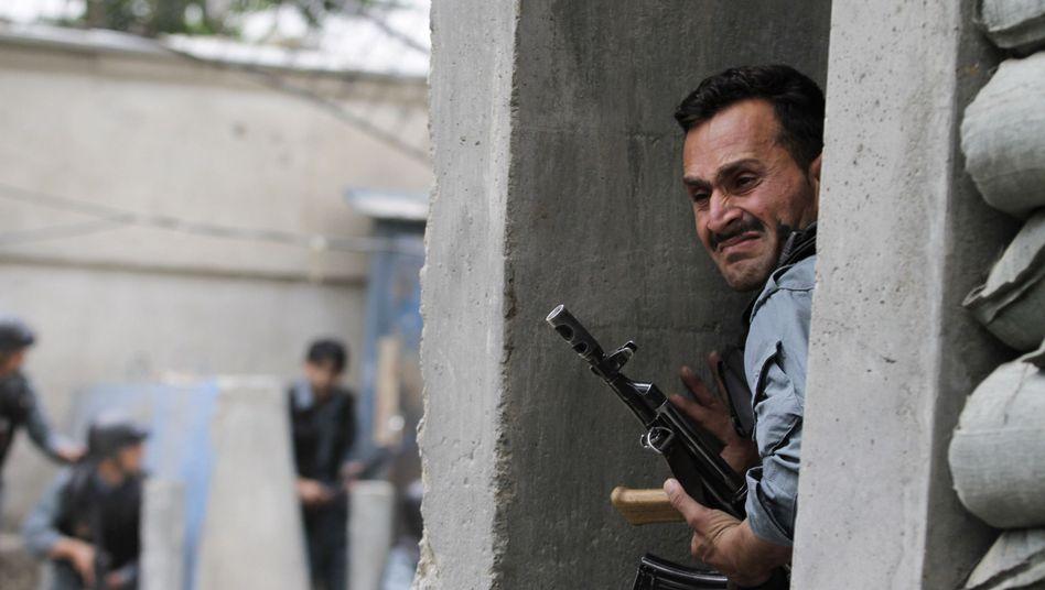 Ein afghanischer Polizist sucht Deckung: Bei Kämpfen sind mehrere Taliban getötet worden