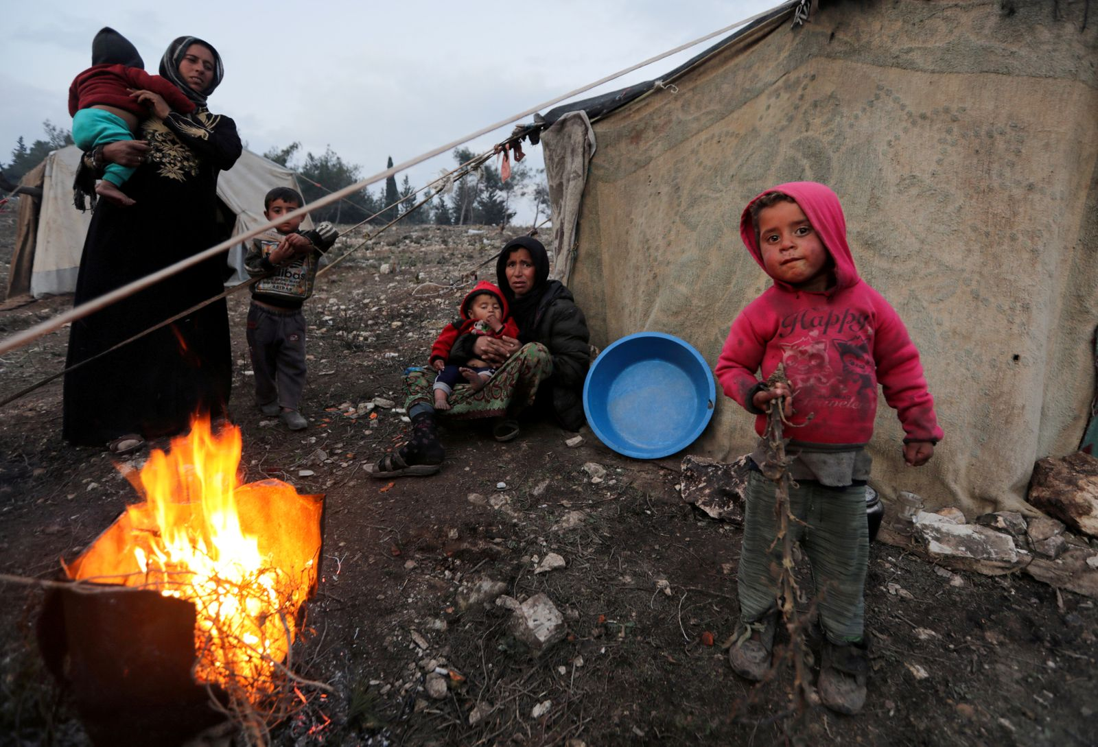 FILE PHOTO: Displaced Syrian women and children, who fled from southern Idlib, gather around a fire in Afrin