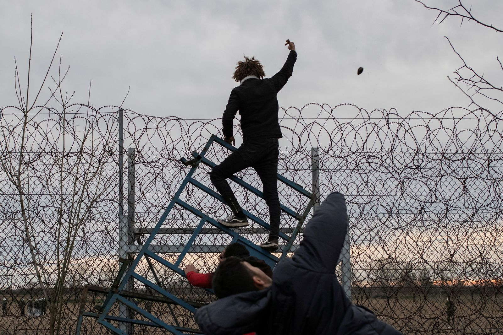 Migrants climb fence at the border as they clash with Greek riot police at Turkey's Pazarkule border crossing with Greece's Kastanies, near Edirne