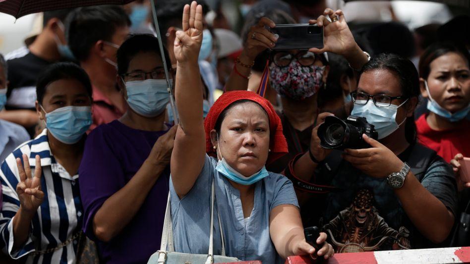 Eine Frau wartet vor dem Insein-Gefängnis in Myanmar. Der Gruß, drei ausgestreckte Finger der rechten Hand, ist zum Symbol des Protests gegen die Militärdiktatur geworden