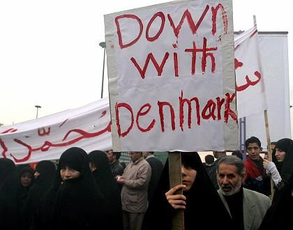 """An Iranian woman holds a placard reading """"Down with Denmark"""" during a protest demonstration in Tehran."""