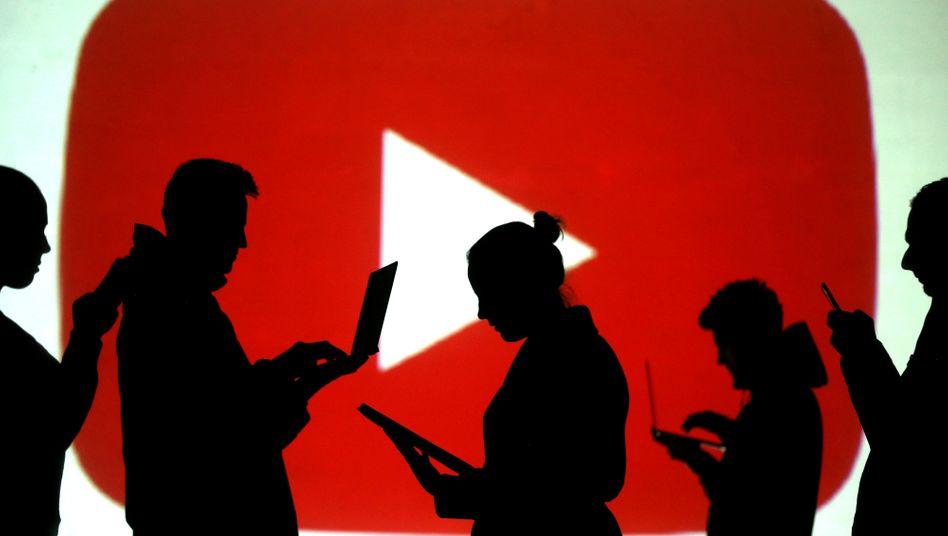 Silhouetten vor einem YouTube-Logo