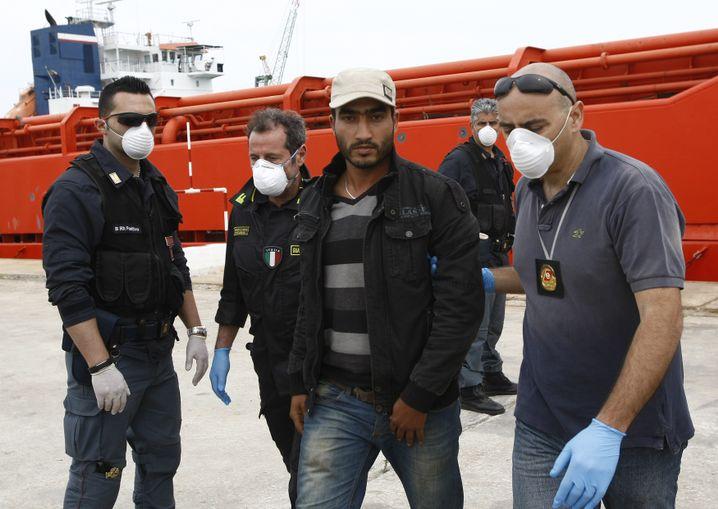 Polizisten nehmen einen mutmaßlichen Schlepper im Hafen von Augusta fest