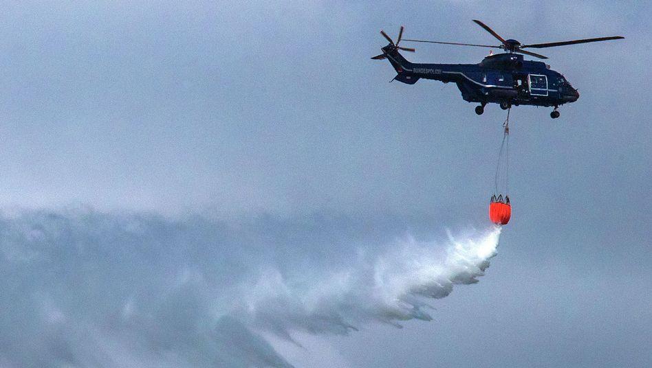 Ein Hubschrauber wirft Löschwasser über dem Großfeuer bei Lübtheen ab