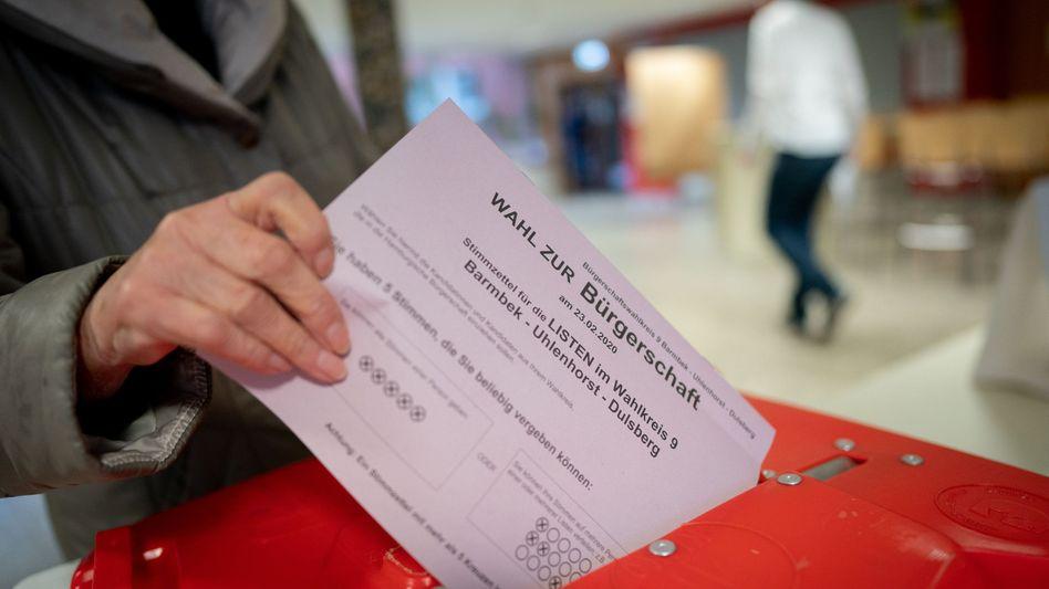 Wählerin mit Stimmzettel in Hamburg