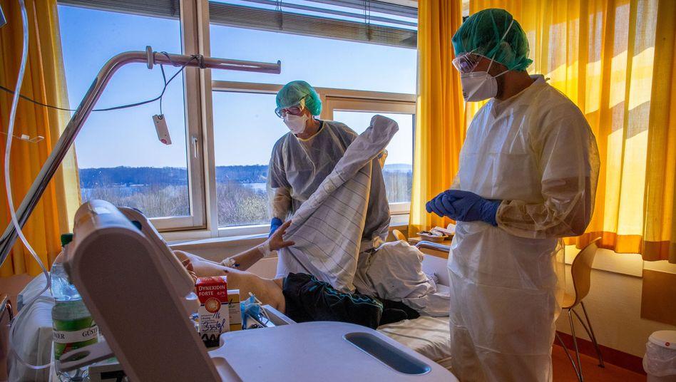 Ein Arzt spricht auf der Isolierstation für Coronavirus-Behandlungen des Schweriner Klinikums mit einem Patienten