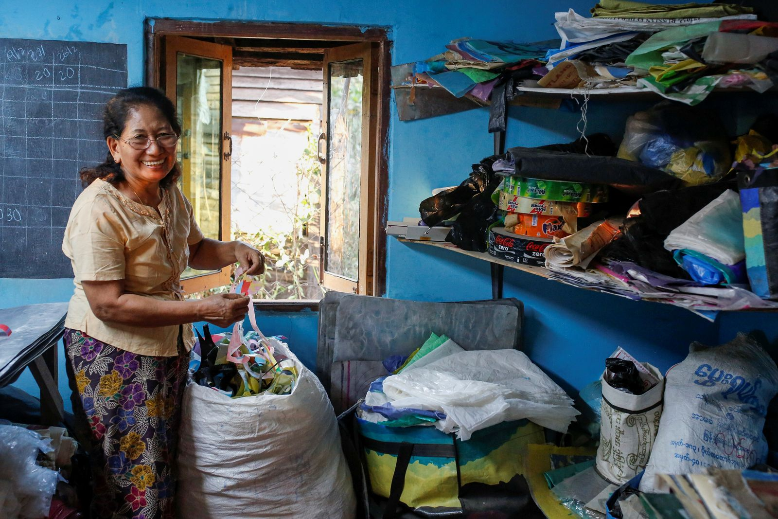 Wendy looks for recycled materials to make into products at a workshop at ChuChu house in Dalla township, Yangon