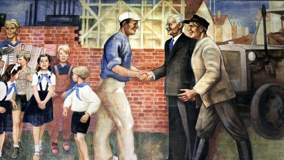 """Junge Pioniere und Werktätige auf einem Wandbild (Ausschnitt) im DDR-Regierungsviertel an der Leipziger Straße in Ostberlin. Nach sowjetischer Vorgabe sollten die Künstler Sujets aus dem Alltag und der Arbeitswelt aufgreifen und sie in idealisierender Weise darstellen (""""sozialistischer Realismus"""")."""