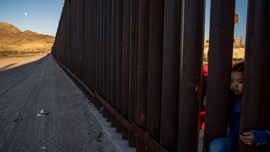 Ein kleines mexikanisches Mädchen steht an einem Metallzaun an der Grenze zu den USA (Archivbild)