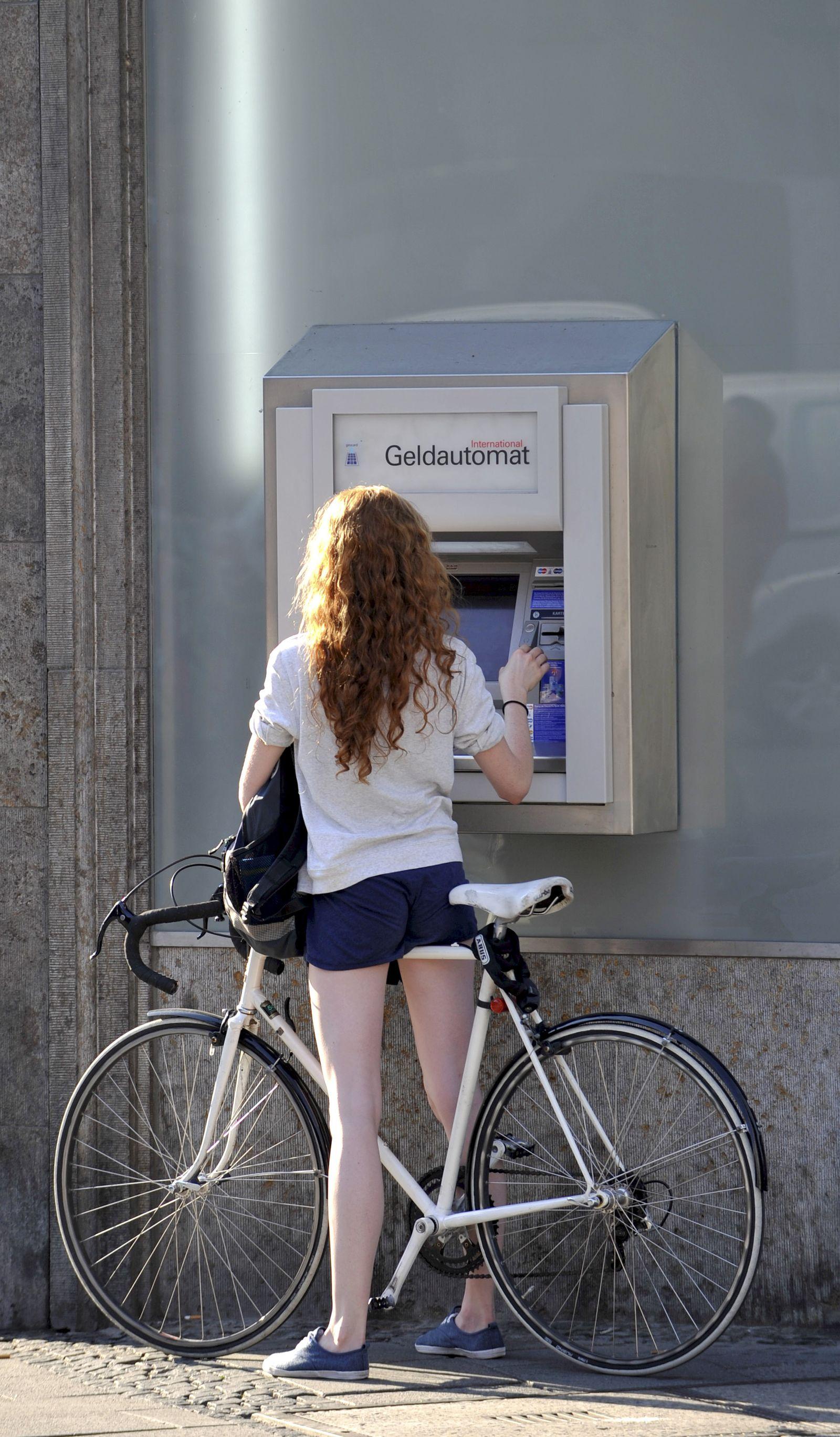 Alltagstaugliche Rennräder/ Frau mit Rennrad am Geldautomat