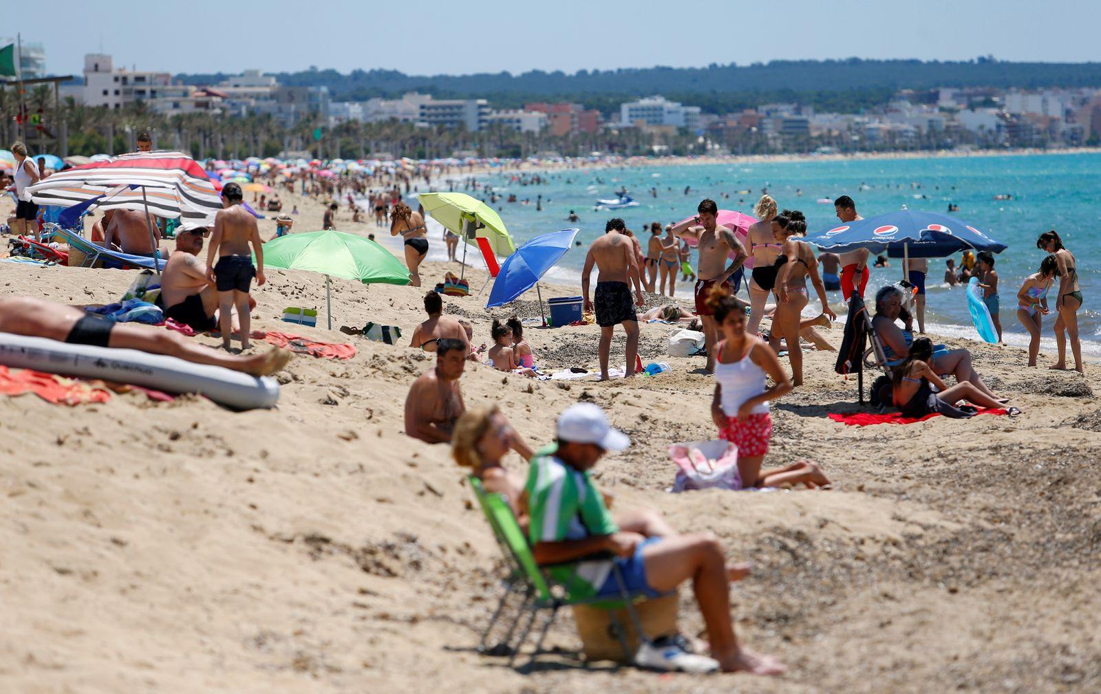 People sunbathe on Playa de Palma beach in Palma de Mallorca