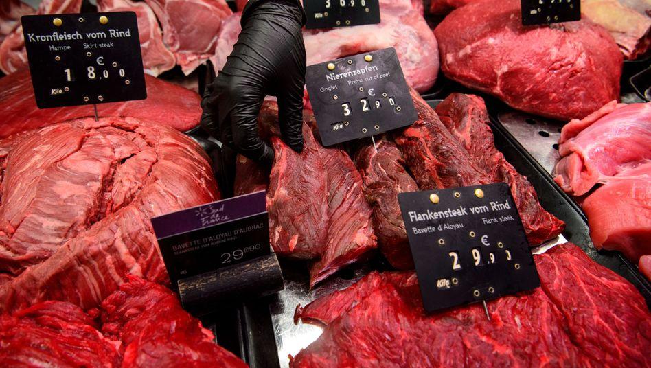 Eine Verkäuferin greift in die Fleischtheke eines Supermarkts. Durchschnittlich knapp 60 Kilogramm Fleisch isst jeder Deutsche im Jahr.