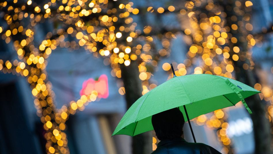 Ein Fußgänger läuft am frühen Morgen mit einem grünen Regenschirm durch Stuttgart