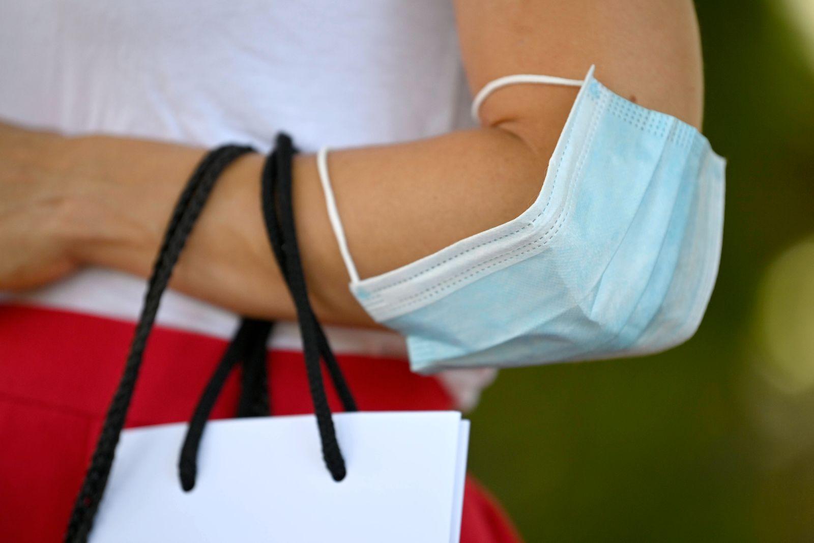 Frau trägt Mundschutzmaske über Ellbogen, Shopping, Corona-Krise, Deutschland Coronavirus *** Woman wears face mask ove