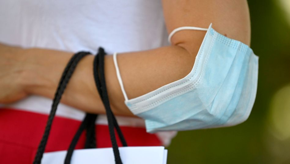 Frau mit Mundschutz über dem Ellenbogen: Künftig soll ein Bußgeld bekommen, wer sich nicht an die Maskenpflicht hält