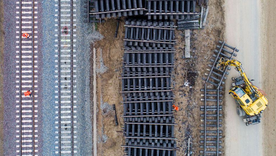 Arbeiter zerlegen mit einem Bagger alte Bahnschienen bei einer Sanierung