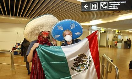 Belgian students repatriated from Mexico pose with a sombreros and surgical masks upon their arrival at Brussels Airport May 5, 2009. They are among about 100 Belgian interns repatriated due to the outbreak of the H1N1 virus in Mexico, previously known as swine flu.