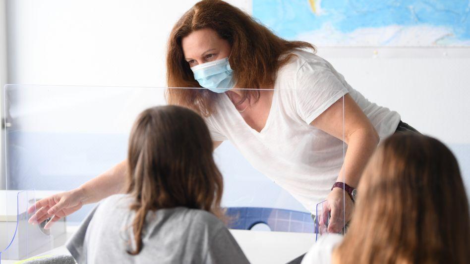 Lehrerinnen und Lehrer mussten während der Pandemie immer wieder improvisieren. Zum Beispiel unterrichteten sie hinter Plexiglas und mit Masken (Archiv)