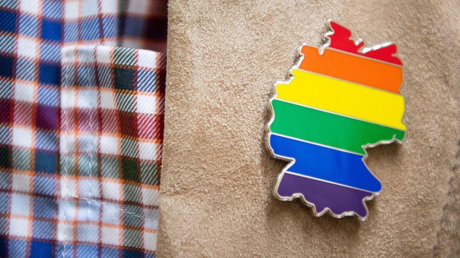 Ein Mann trägt einen regenbogenfarbenen Deutschland-Pin