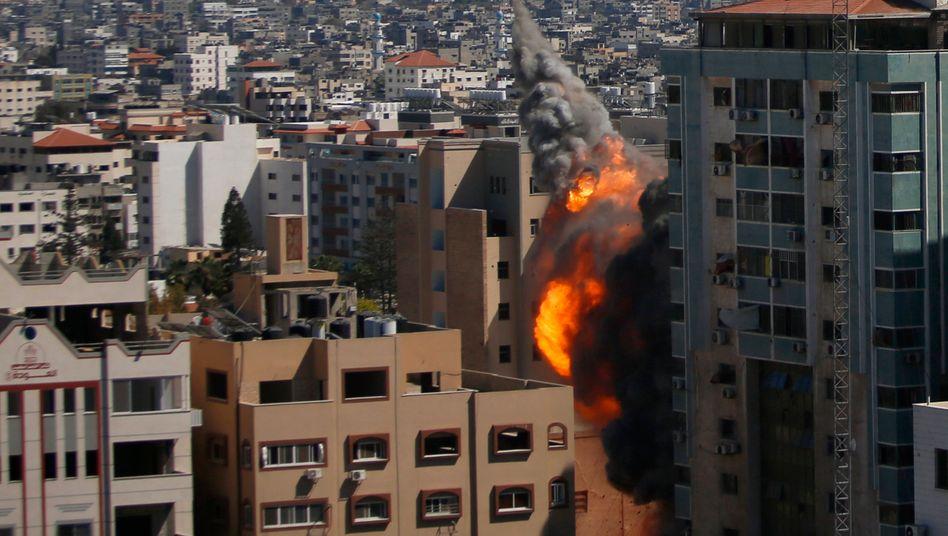 Palästinensische Autonomiegebiete, Gaza-Stadt: Rauch und Flammen steigen aus einem Gebäude auf, in dem verschiedene internationale Medien untergebracht sind