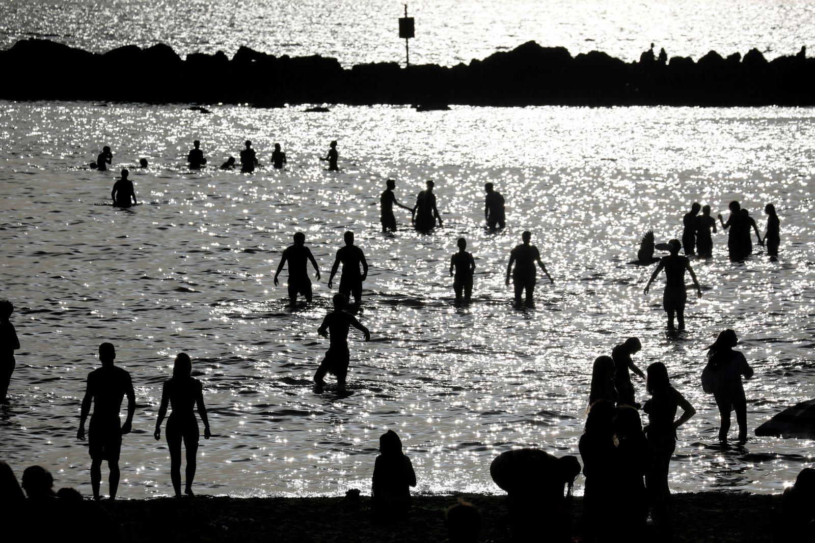 Israelis bathe in the water of the Mediterranean sea in Tel Aviv as coronavirus disease (COVID-19) restrictions ease in Israel