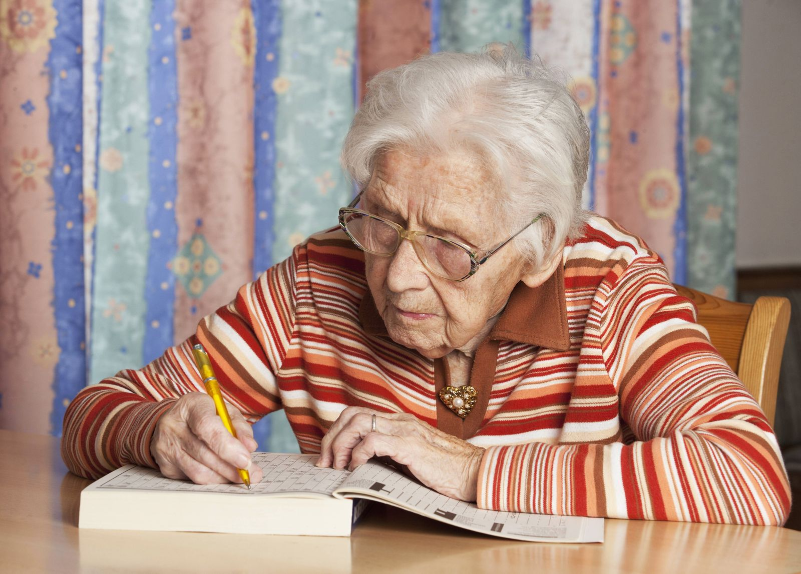 Portrait of senior woman with crossword puzzle model released Symbolfoto PUBLICATIONxINxGERxSUIxAUTx