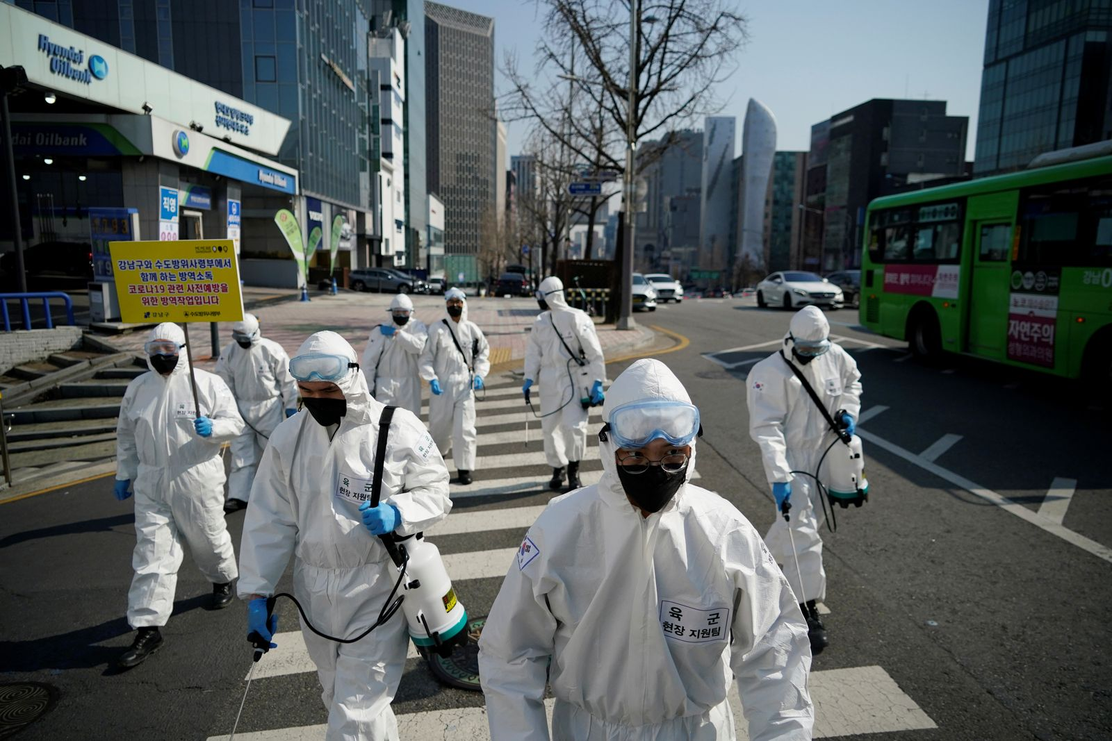 South Korean soldiers in protective gear sanitize a street at a shopping district in Seoul