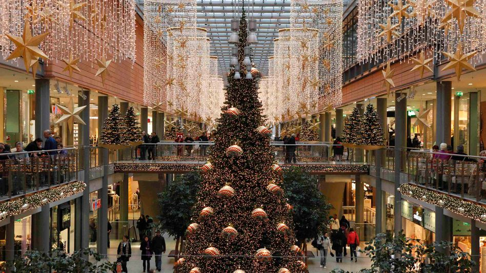 Shoppers walk among illuminated Christmas decorations in a shopping mall at Berlin's Potsdamer Platz.