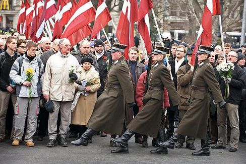 An honor guard leads the way as veterans of the Waffen SS marched through Riga on Monday.