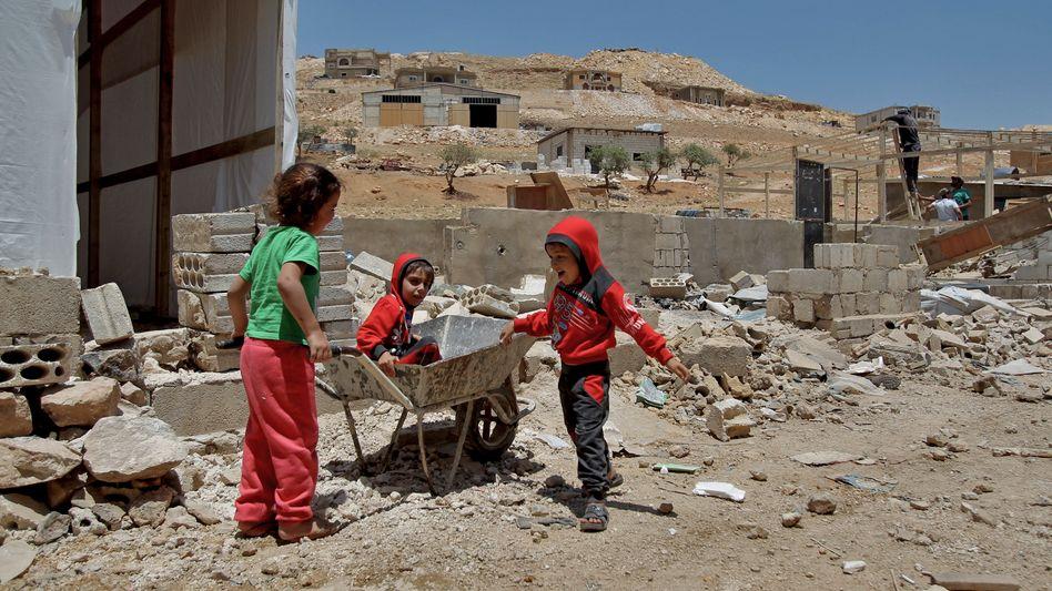 Libanon: Syrische Flüchtlingskinder spielen in den Trümmern von abgerissenen Zementunterkünften in Arsal