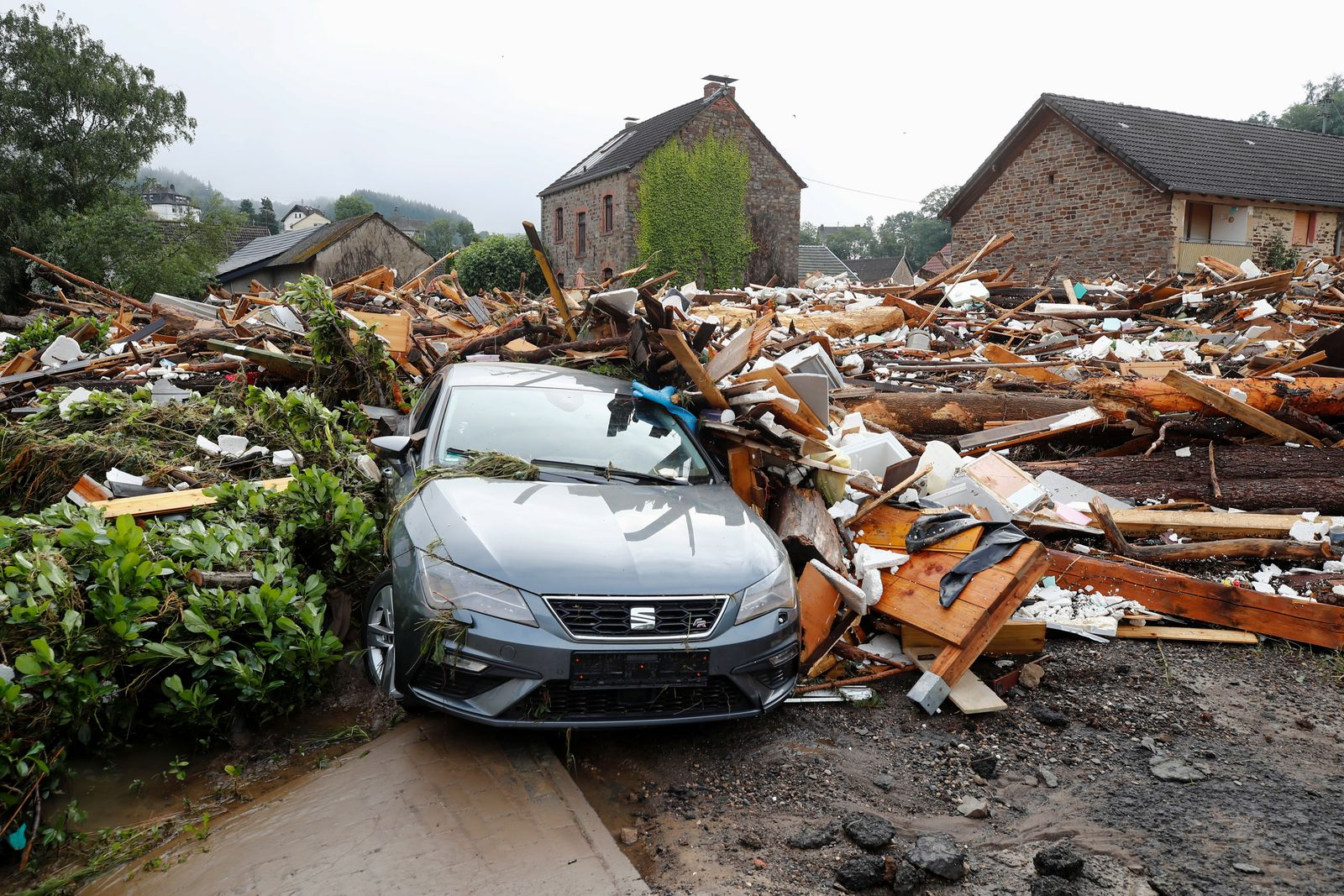 A car partly covered with debris from collapsed houses is seen in Schuld