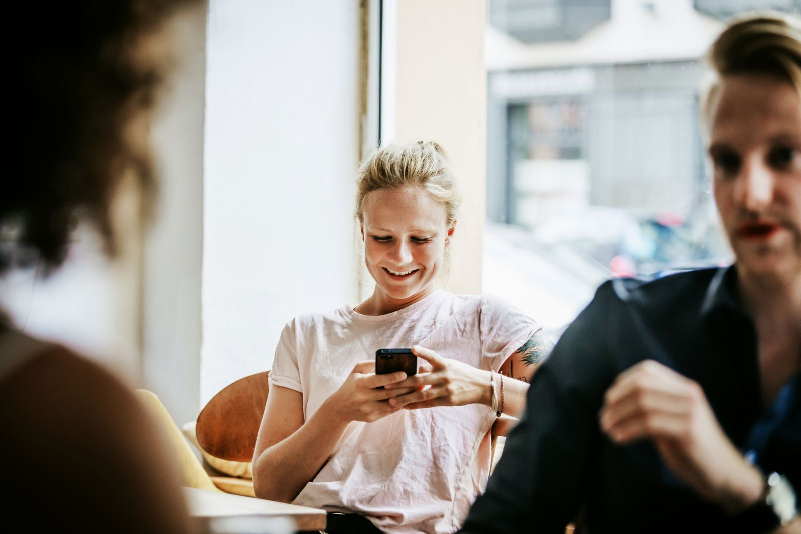 Young Woman Smiling While Messaging Friends On Smartphone In Cafe