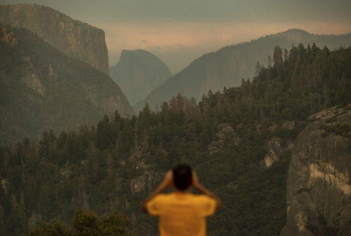 Ein Tourist fotografiert den von Rauchwolken umgebenen Half Dome im Yosemite-Park