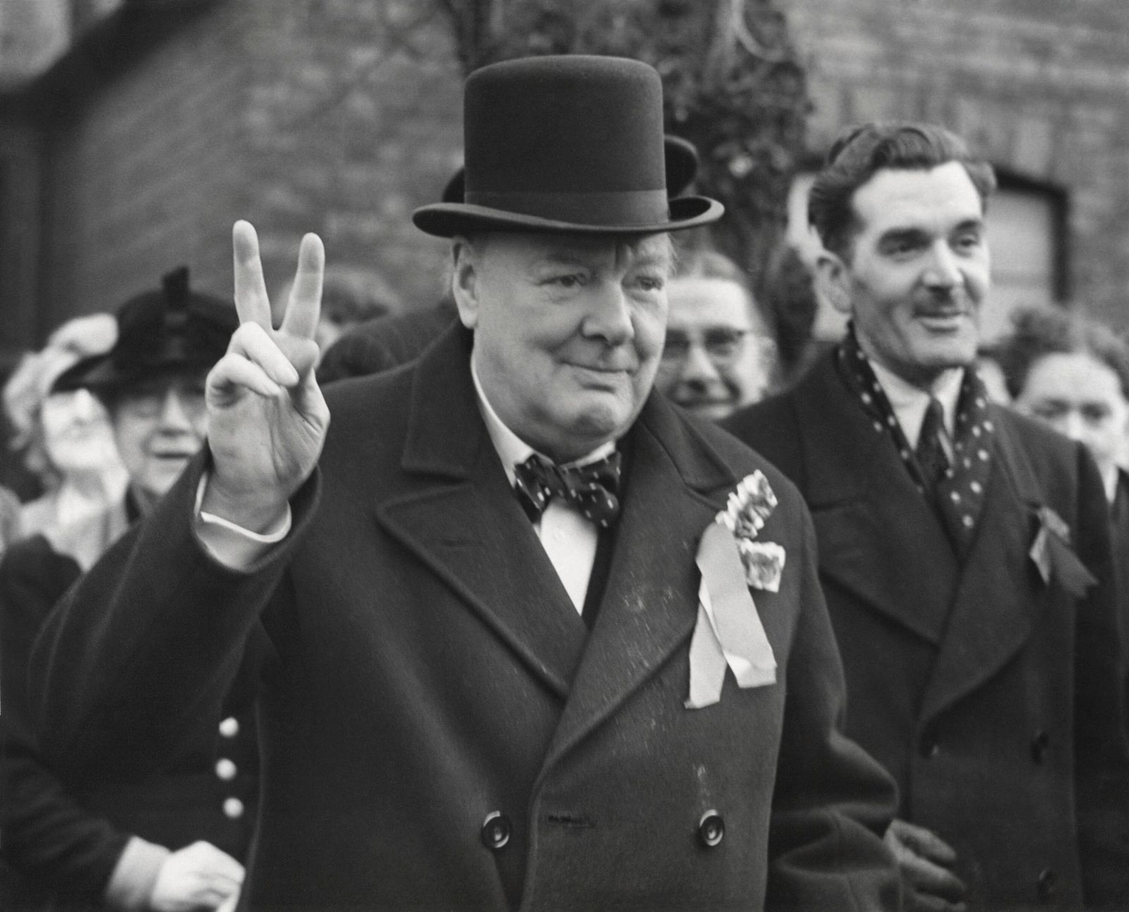 Conservative Party Leader Winston Churchill gives his familiar victory sign. He was making a last-minute campaign tour b