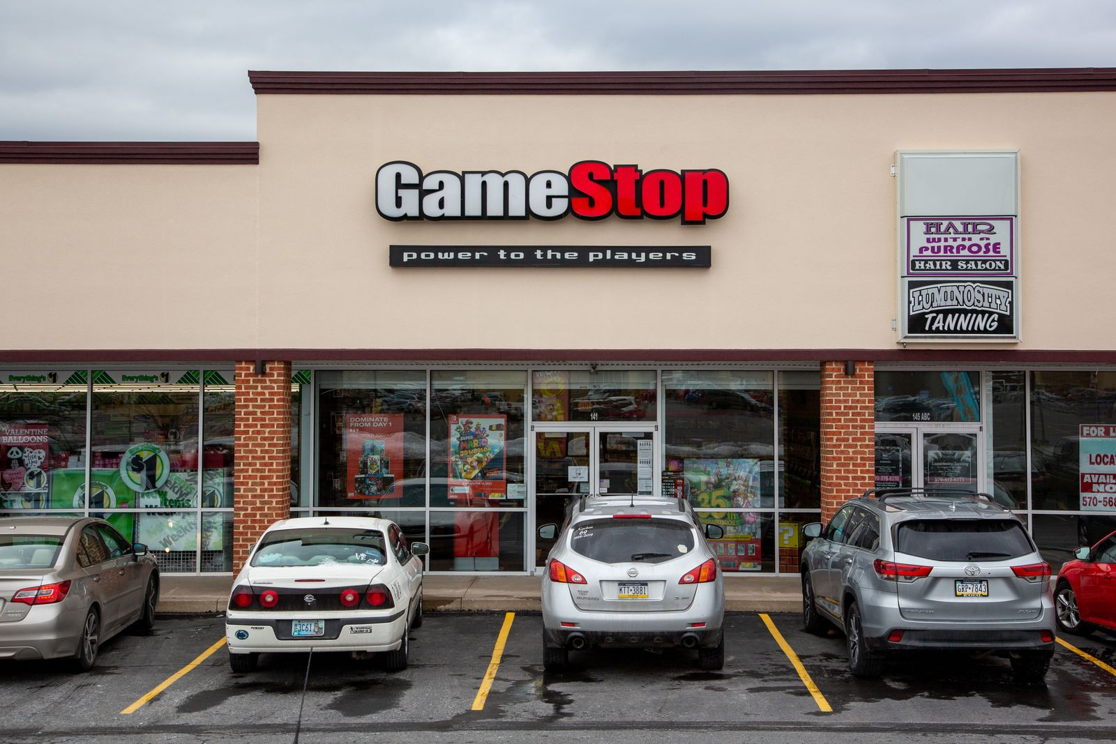 Vehicles seen parked in front of the GameStop store at the