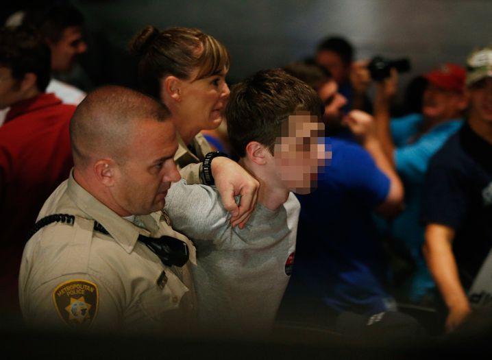 Polizisten führen den Verdächtigen ab