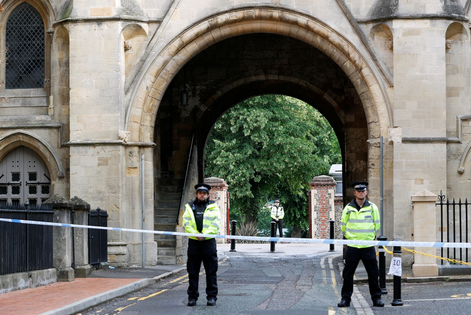 Police officers stand behind the cordon at the scene of multiple stabbings in Reading