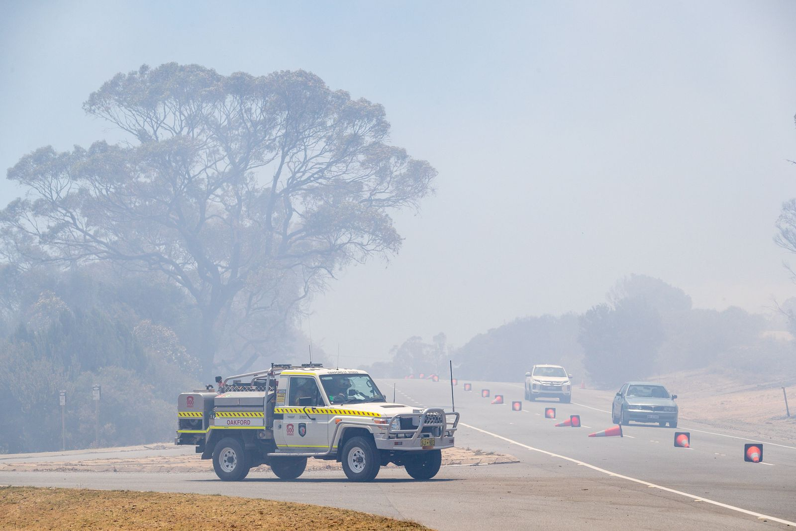 WA BUSHFIRES, Emergency vehicles drive through bushfire smoke on Patterson Road in Kwinana, south of Perth on Monday, J