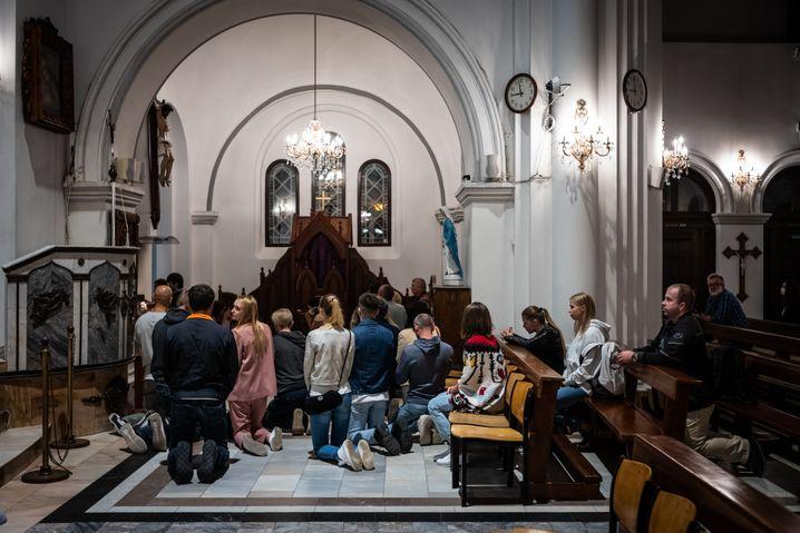 """Katholische Gläubige beten in der """"Kirche des heiligen Simon und der heiligen Helena"""" in Minsk. Dutzende hatten sich am 26. August in das Gotteshaus geflüchtet und waren von Omon-Einsatzkräften dort eingesperrt worden. Erzbischof Tadeusz Kondrusiewicz verurteilte die Aktion scharf."""