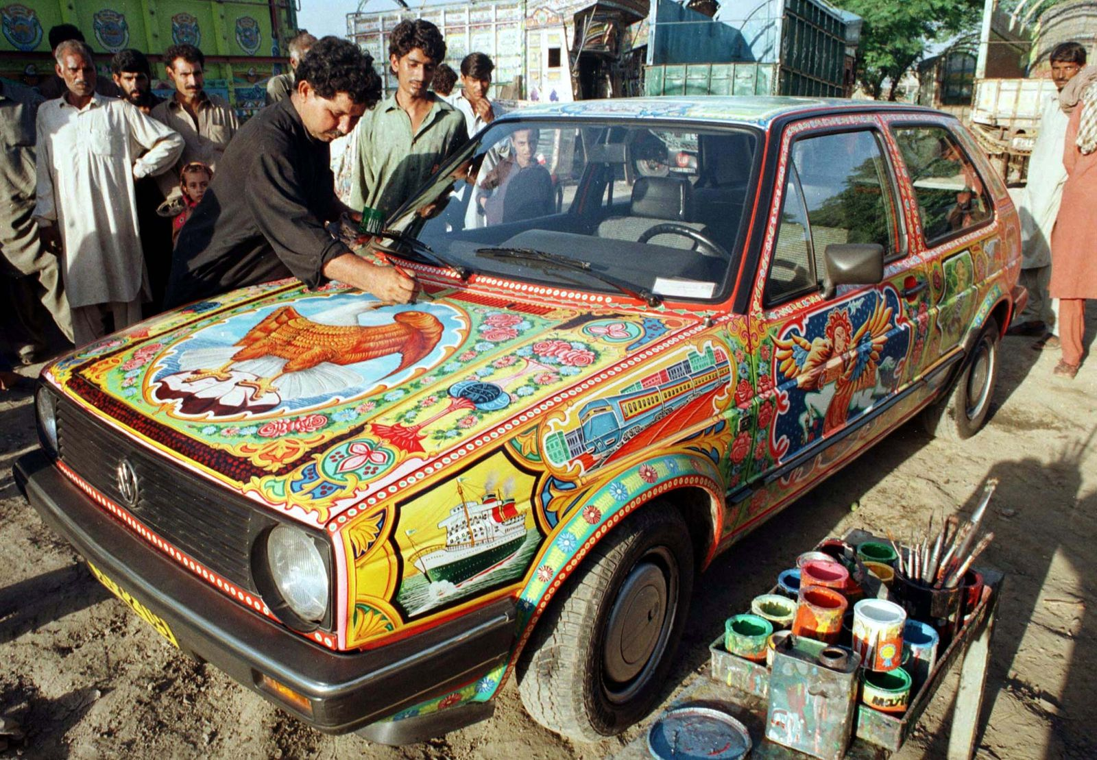 Ejaz Hussain, a Pakistani painter, puts the final touches to the paintwork on a Volkswagen Golf car ..