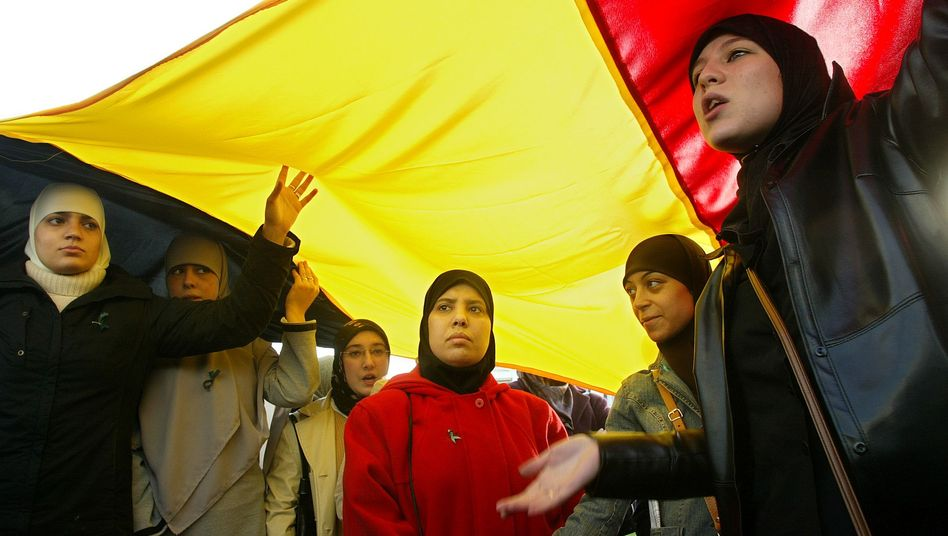 Veiled Muslim women stand underneath the Belgian national flag at a demonstration against a veil ban in schools in 2004.