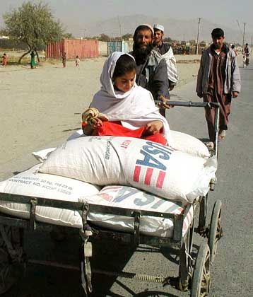 Ein afghanisches Mädchen transportiert Lebensmittel, die das US-Welternährungs- programm für die Zivilbevölkerung bereitgestellt hat, durch Kabul