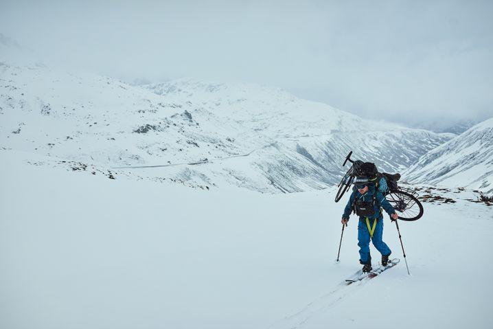 Max Kroneck mit Gepäck und Fahrrad bei einer Skitour