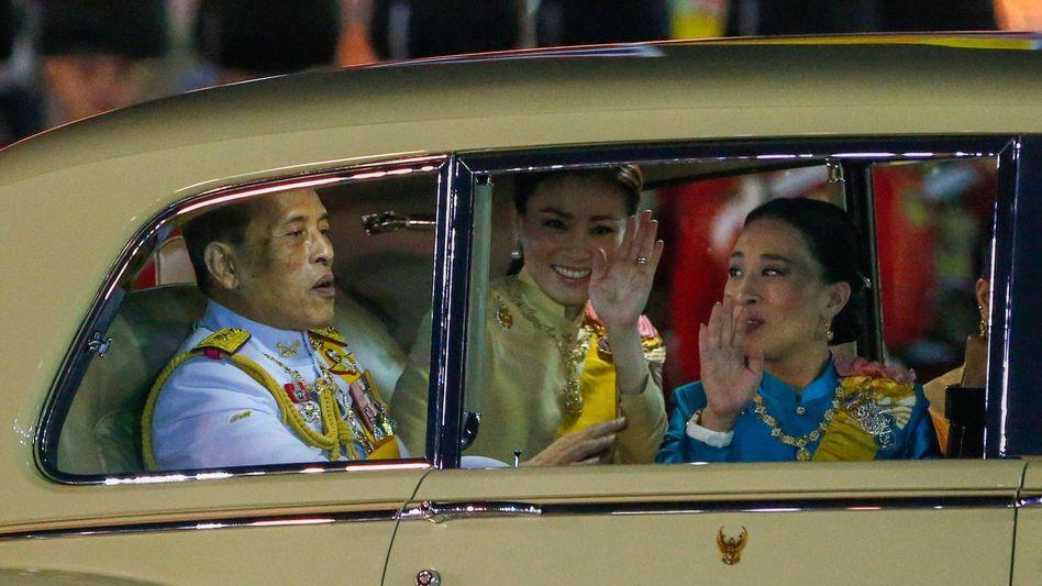 König Rama X. Anfang Dezember in Bangkok mit Königin Suthida (M.) und Tochter Bajrakitiyabha: »Welche Steuern muss er bezahlen? Arbeitet er von hier?«