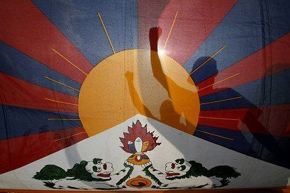 How long will they wait? Tibetans in exile are seen through a national flag of Tibet as they take part in a peace rally.
