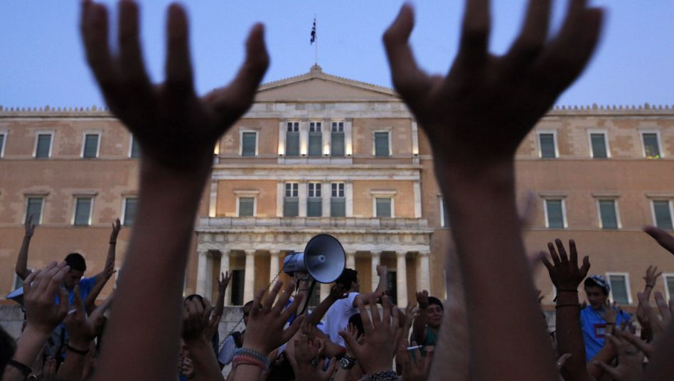 Protesters raise their hands at a demonstration against austerity measures in Athens.