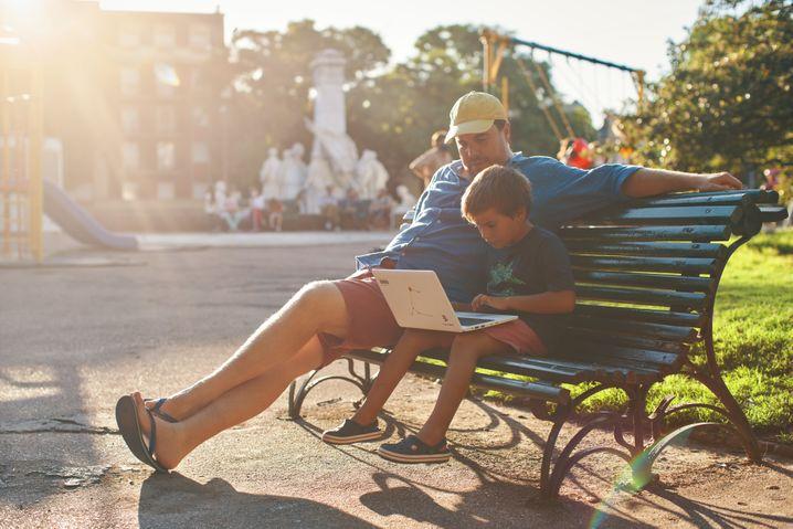 Der siebenjährige Francisco und sein Vater machen Schulaufgaben im Freien