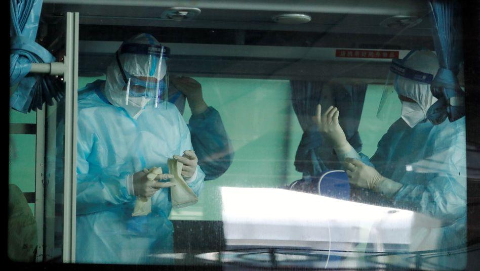 Startklar zur Aufarbeitung: Medizinisches Personal in Wuhan wartet in einem Bus auf die Ankunft der WHO-Truppe