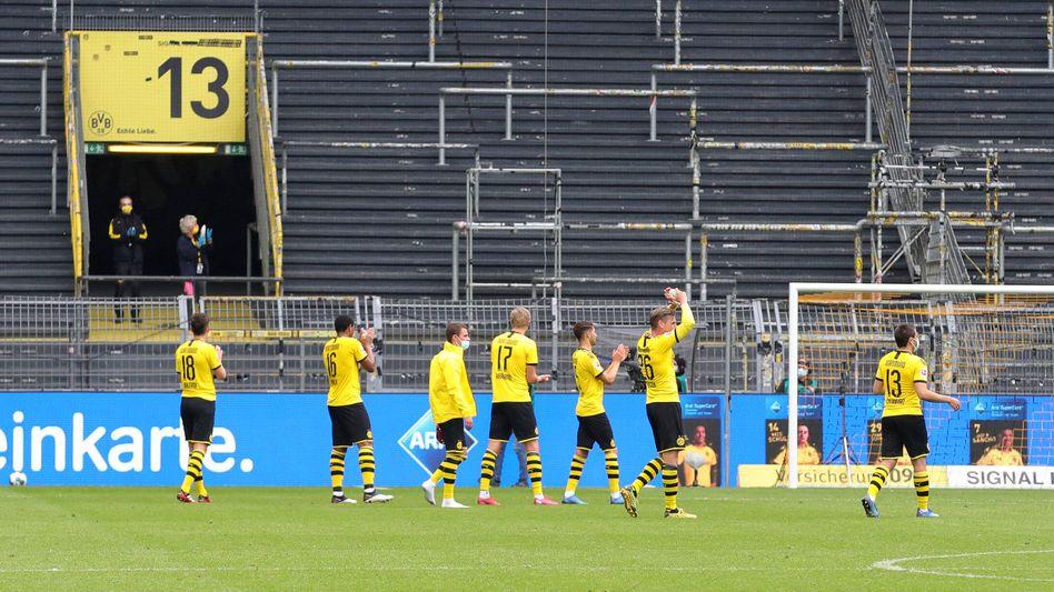 Dortmunds Profis jubeln nach dem Sieg gegen Schalke vor der leeren Südtribüne